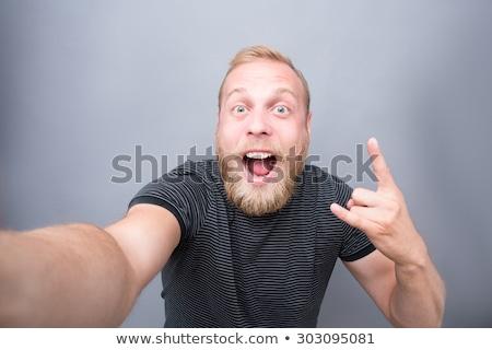 Happy Bearded man in shirt making selfie in studio Stock photo © deandrobot