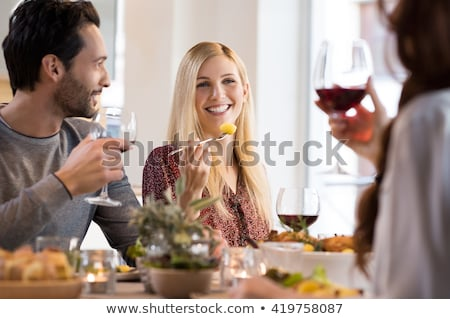 woman at party setting out food and smiling stock photo © monkey_business