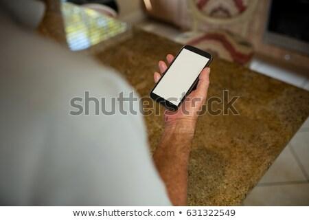 Mid-section of senior man holding mobile phone in the ktchen Stock photo © wavebreak_media