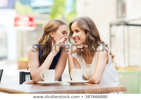 smiling young women drinking coffee and gossiping stock photo © dolgachov