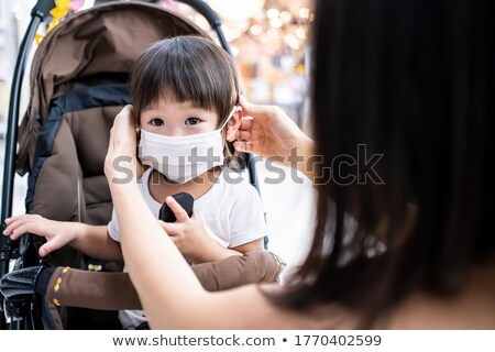 Stock photo: Girl looking at mother taking care of baby in shop