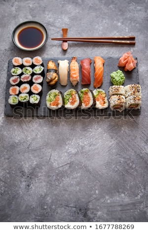 composition of different kinds of sushi rolls placed on black stone board stock photo © dash