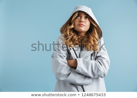 Image of dissatisfied woman 20s wearing raincoat with hood looki Stock photo © deandrobot