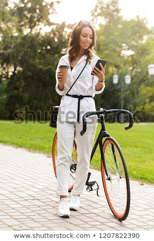 cute young woman walking in park with bicycle holding coffee stock photo © deandrobot