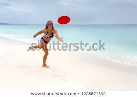 vivacious australian girl playing frisbee idyllic beach paradise stock photo © lovleah