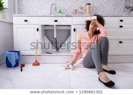 tired african woman holding broken sink pipe stock photo © andreypopov