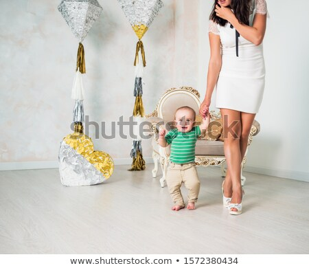 one hand baby boy learning to walk with the help of her mother Stock photo © Lopolo