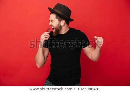 Cheerful bearded man in shirt and headphones listening music Stock photo © deandrobot