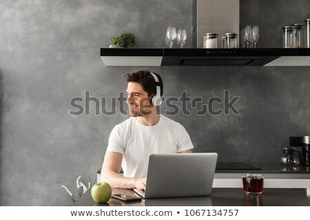 Photo of joyous adult man 30s in casual clothing ,and headphones Stock photo © deandrobot