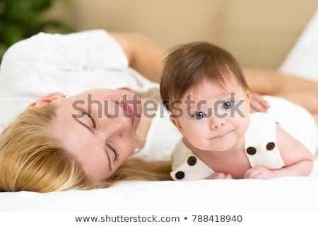 portrait of parent with her 3 month old baby in bedroom sleeping stock photo © lopolo