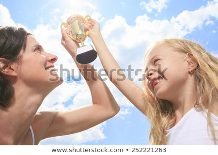 Happy mother and daughter holding a trophy high up Stock photo © Lopolo