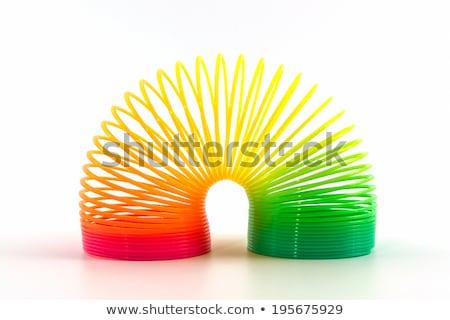 Flexible plastic rainbow spring on a blue background. Stock photo © artjazz