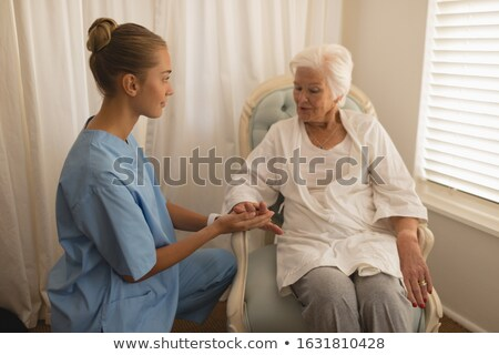 beautiful female physician consoling senior woman and holding her hand at home stock photo © wavebreak_media