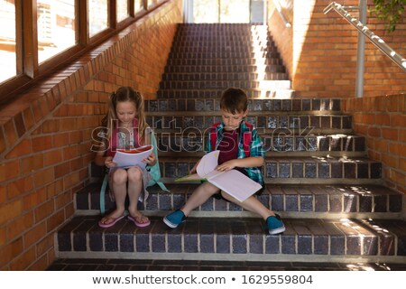 Front view of Caucasian schoolkids reading book while sitting on stairs outside of elementary school Stock photo © wavebreak_media