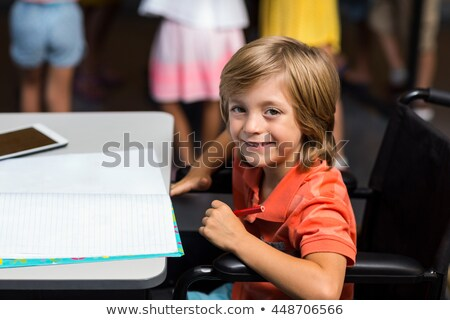 High angle view of disable schoolboy looking at camera in classroom of elementary school Stock photo © wavebreak_media