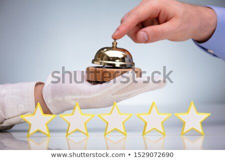 Five Stars In Front Of Person Ringing Service Bell Stock photo © AndreyPopov