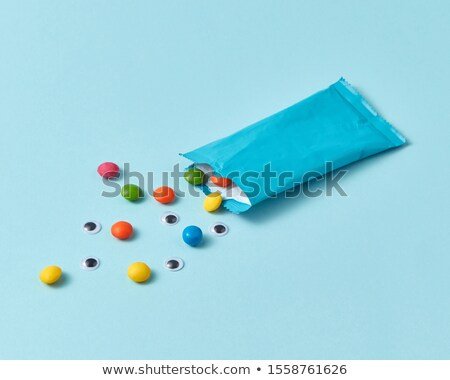 Paper box with colorful candy and pupils on a light blue background. Stock photo © artjazz