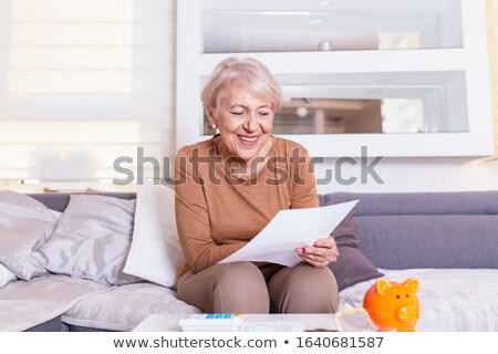 sad senior woman reading letter and crying Stock photo © dolgachov