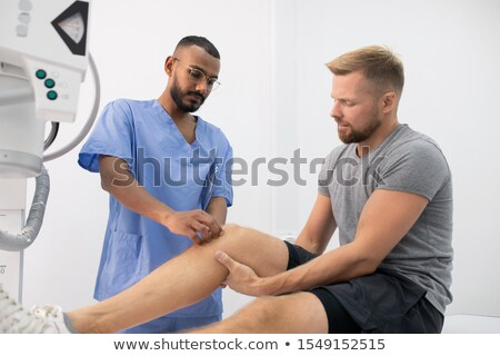young doctor in uniform massaging sick knee of one of patients in hospital stock photo © pressmaster