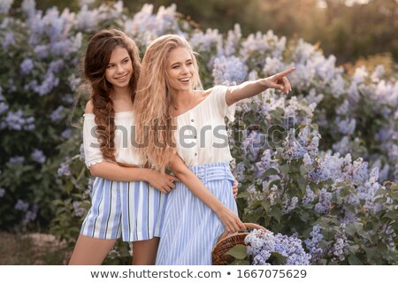 Two young girls dressed in beautiful clothes stand against the background of lilac bushes Stock photo © ElenaBatkova