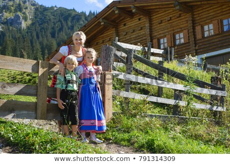 Young Bavarian boy with pretzel in meadow Stock photo © Kzenon