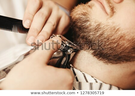 Barber trimming beard of customer Stock photo © Kzenon