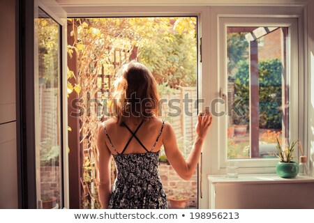 Beautiful woman looks out of the doorway Stock photo © pekour