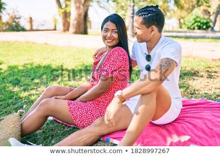 Foto stock: Dos · mujeres · sonriendo · sesión · hierba · ciudad