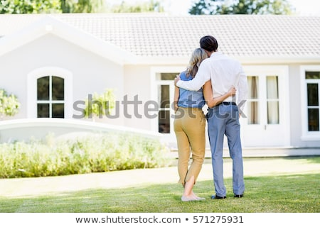 Rear view of a loving couple standing with arms around  Stock photo © dacasdo