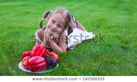 Lovely girl with pigtails in a garden with a plate of vegetables Stock photo © travnikovstudio