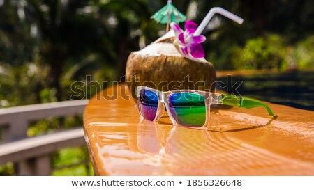 sunglasses near coco nut with a straw on the beach Stock photo © feedough