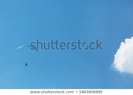 Silhouette of paraglider and blue sunny sky Stock photo © BSANI