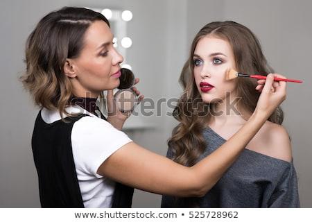 Makeup artist hand working on beautiful blonde face stock photo © lunamarina