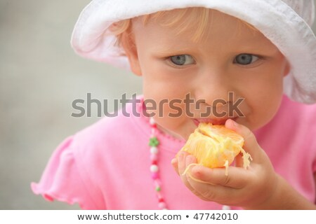Little girl wearing panama hat is eating orange. focus on orange in hand. stock photo © Paha_L