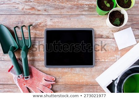close up of tablet pc and garden tools on table Stock photo © dolgachov