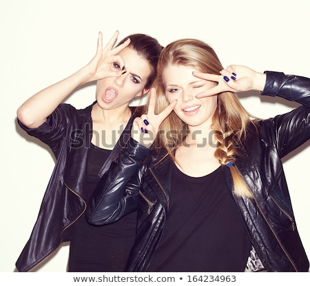 two women in leather jackets looking at their friend stock photo © feedough