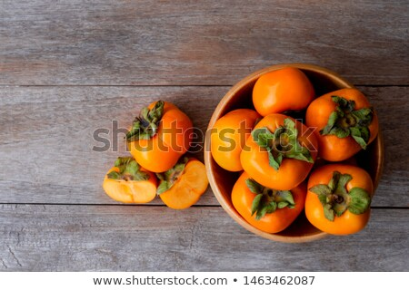 Stock photo: Fresh persimmons fruit in bowl