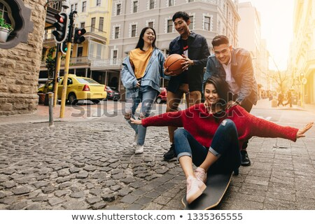 group of four young asian people sitting together outdoors at a stock photo © kzenon