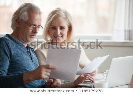 Woman and senior man looking at papers Stock photo © IS2