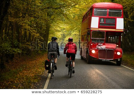 Couple cycling next to bus in country Stock photo © IS2