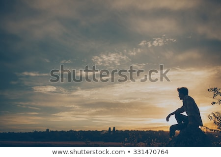 Young man sitting by a cliff Stock photo © IS2