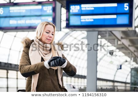 Woman looking at wristwatch in train station as her train has a delay Stock photo © Kzenon