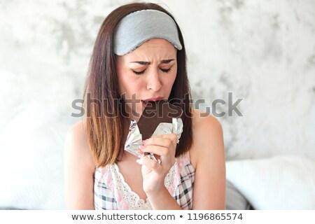 Cheerful sad young craing woman eating chocolate bar and keeping Stock photo © dashapetrenko