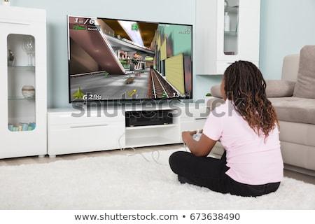 Fille jouer jeu vidéo télévision séance tapis Photo stock © AndreyPopov