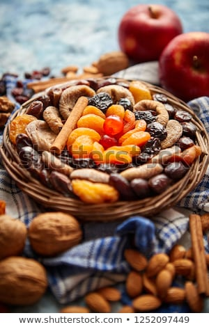 Composition of dried fruits and nuts in small wicker bowl placed on stone table Stock photo © dash