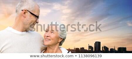 senior couple hugging over evening tallinn city Stock photo © dolgachov