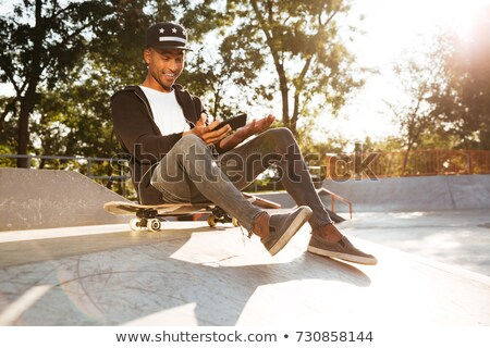 Cheerful young skater guy sit in the park with skateboard using mobile phone. Stock photo © deandrobot