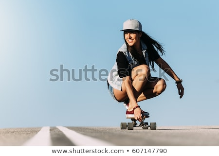 Stock photo: smiling teenage girl with skateboard on street