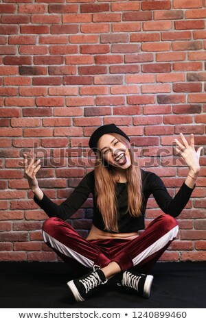 Photo of trendy hip hop dancer or sporty woman, sitting on floor Stock photo © deandrobot