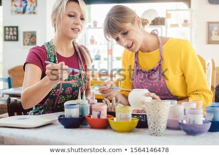 Two girl friends painting their own handmade ceramics Stock photo © Kzenon